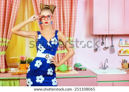 Pretty pin-up girl on a pink kitchen. Retro style. Fashion. - stock photo