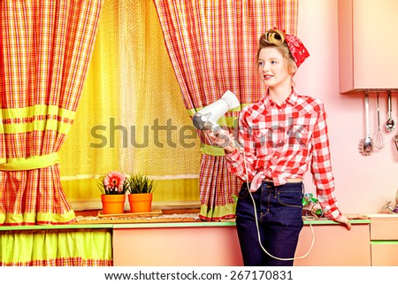Pretty pin-up girl teenager styles her hair with a hair dryer on a pink kitchen. Beauty, youth fashion. Pin-up style. - stock photo