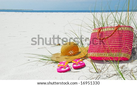 Pretty pink beach items on deserted shore - stock photo
