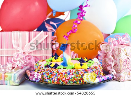 Pretty pink birthday cake with the number 1 candle.  Cake is surrounded by gifts, party balloons, poppers and ribbons. - stock photo