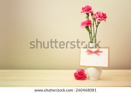 Pretty Pink Carnation Flowers on White Vase with Blank Greeting Card on Wooden Table with Light Brown Wall Background - stock photo