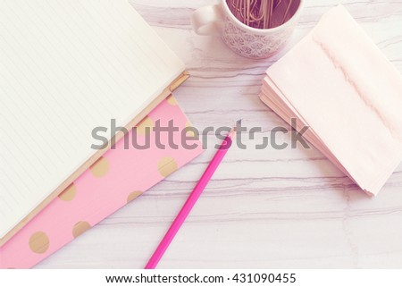 Pretty pink desktop over head view with pink office supplies  room for copy - stock photo