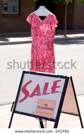 Pretty pink dress advertising a major clearance sale on the sidewalk of a small town. - stock photo