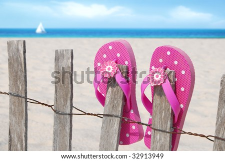Pretty pink flip flops on beach fence with sailboat in distance - stock photo