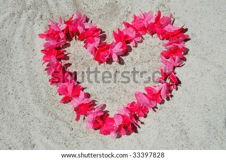 Pretty pink heart lei laying on sand - stock photo