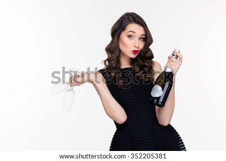 Pretty playful curly young woman in retro style offering champagne and holding two glasses - stock photo