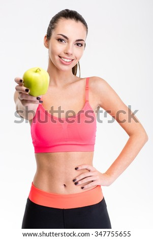 Pretty positive young sportswoman in pink top and black leggings giving an apple over white background - stock photo