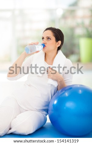 pretty pregnant woman drinking fresh water after workout - stock photo