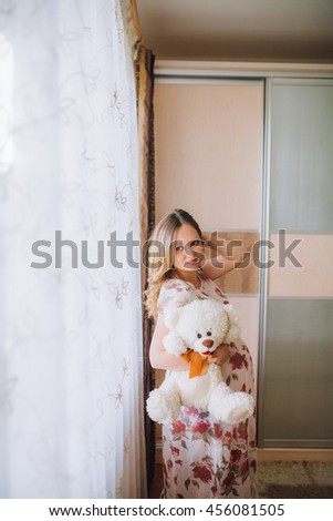 Pretty pregnant woman lying on the bed and touching her stomach. Woman stay near window. with teddy bear toy. Make up. - stock photo