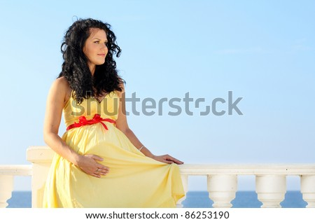 Pretty pregnant woman over sky in yellow dress - stock photo