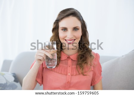 Pretty pregnant woman showing glass of water sitting on couch in living room at home