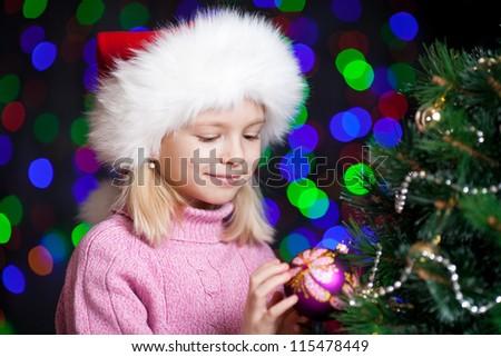 pretty preschool girl decorating Christmas tree over bright festive background - stock photo