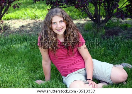 pretty preteen girl with braces outside in the yard