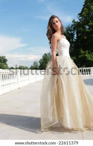 pretty princess in white-golden gown under blue sky