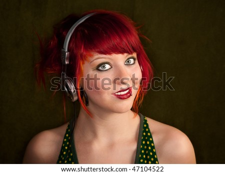 Pretty punk girl with brightly dyed red hair listening to music