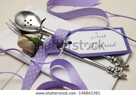 Pretty purple polka dot wedding table place setting on white shabby chic table with Just Married tag. Close up. - stock photo