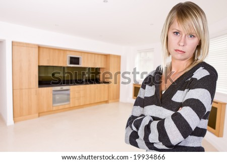 Pretty Real Estate Agent Showing Luxury Apartment's Kitchen - stock photo