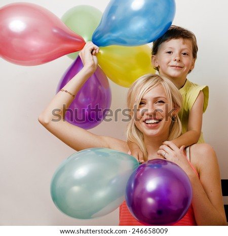 pretty real family with color balloons on white background, blond woman with little boy on birthday party isolated