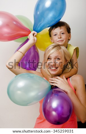 pretty real family with color balloons on white background, blond woman with little boy on birthday party isolated smiling holiday