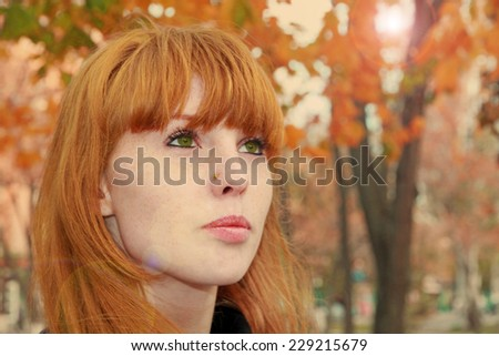 Pretty red hair girl face with freckles against red autumn foliage.Tonal correction. - stock photo