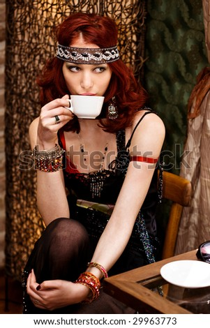 pretty red hair woman drinks coffee in cafe - stock photo