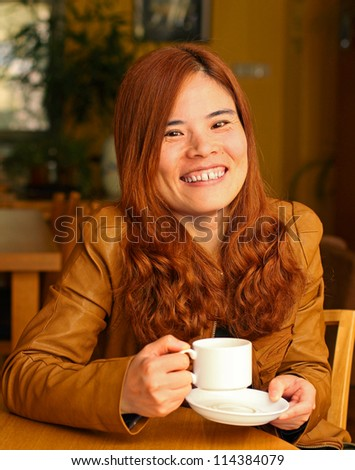 Pretty Red Haired Asian Woman Laughing over a Cup of Coffee - stock photo