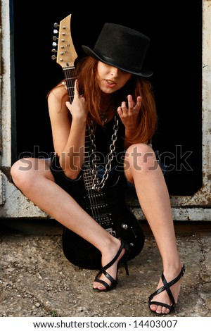 Pretty red-haired girl with electric guitar in a black hat. - stock photo