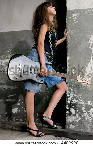 Pretty red-haired girl with electric guitar on the wall background. - stock photo