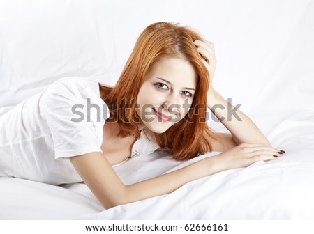 Pretty red-haired sleeping woman in white nightie lying in the bed