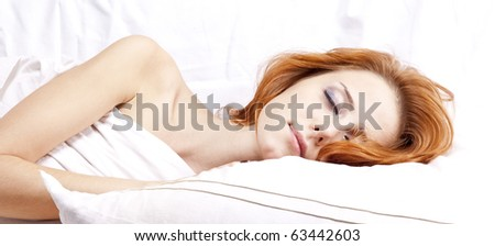 Pretty red-haired sleeping woman in white nightie lying in the bed - stock photo