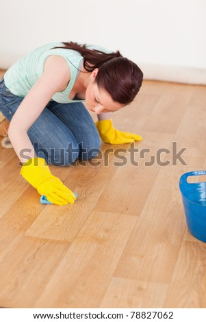 Pretty red-haired woman cleaning the floor while kneeling at home - stock photo