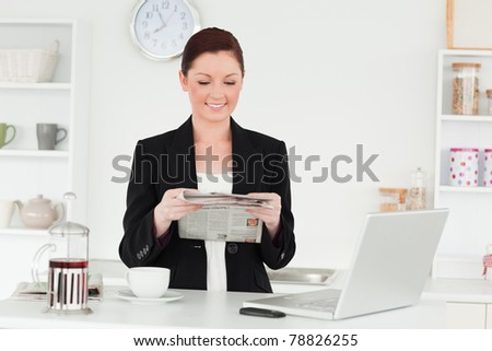 Pretty red-haired woman in suit reading the newspaper in the kitchen in her apartment - stock photo