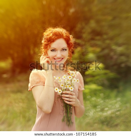 Pretty red-haired woman smiling with camomiles in hands - stock photo