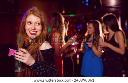 Pretty redhead drinking a cocktail at the nightclub