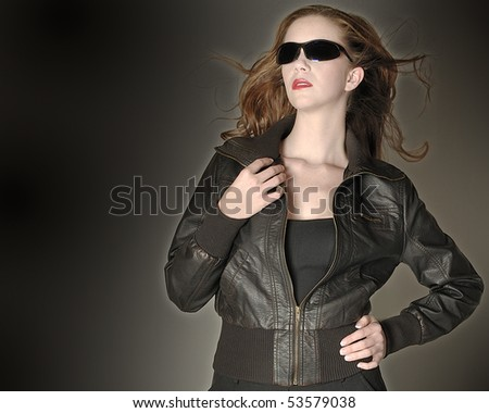 Pretty redhead in leather flight jacket looks towards the sky