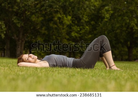 Pretty redhead lying and smiling in park at sunshine - stock photo