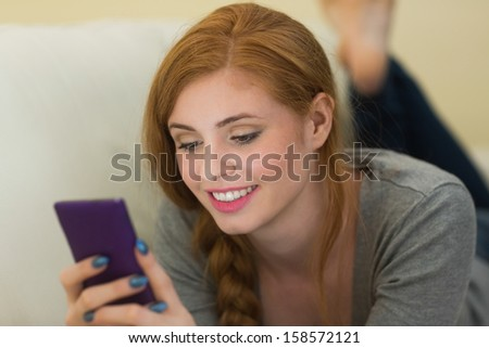Pretty redhead lying on the sofa sending a text at home in the sitting room - stock photo