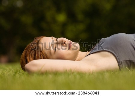 Pretty redhead lying with her eyes closed in park at sunshine