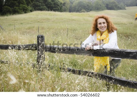 Pretty Redhead Senior Outdoors in Nature Leaning on a Fence - stock photo
