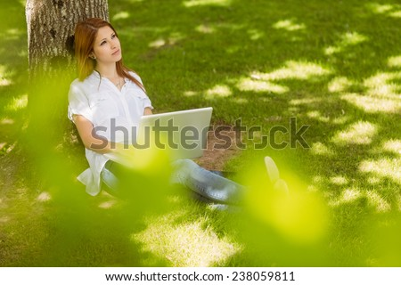 Pretty redhead sitting against a trunk with her laptop in park on a sunny day - stock photo