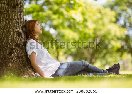 Pretty redhead sitting and thinking in park - stock photo