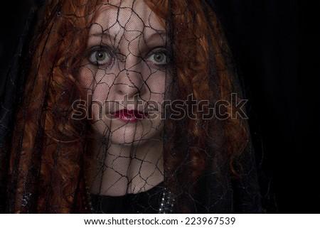 Pretty redhead wearing black dress and black veil  - stock photo