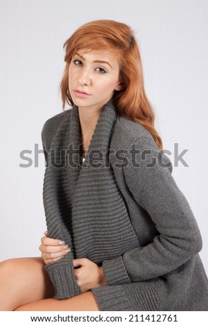Pretty Redhead woman in grey dress, sitting and looking at the camera with serious expression