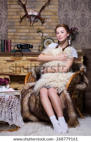 Pretty redhead woman with pigtails sitting on the chair near a fireplace - stock photo