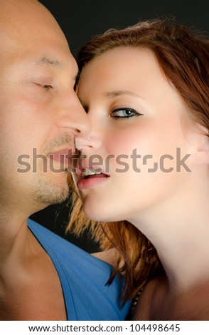 Pretty redheaded girl kissing a man while looking at the camera - stock photo