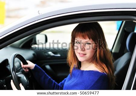 pretty redheaded teen girl driving a car - stock photo