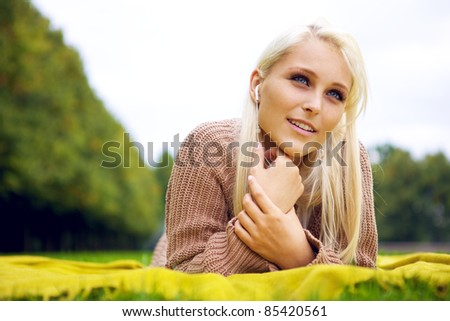 Pretty relaxing woman in park - stock photo