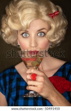 Pretty retro blonde woman in vintage 50s dress with martini - stock photo