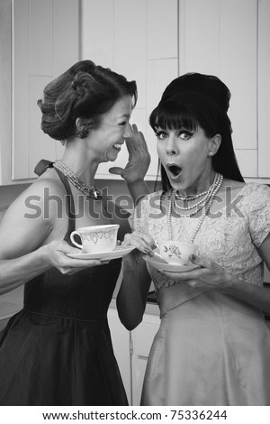 Pretty retro Caucasian women gossiping over coffee in kitchen - stock photo