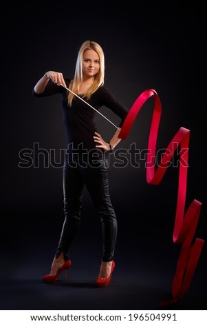 Pretty rhytmic gymnast exercising with ribbon over black background. - stock photo